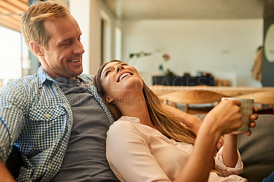 Buy stock photo Shot of a happy young couple enjoying a relaxing coffee break on the sofa at home