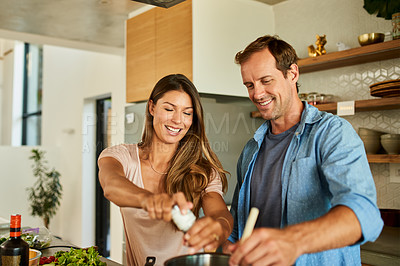 Buy stock photo Cropped shot of an affectionate young couple standing in the kitchen together and preparing lunch for their family