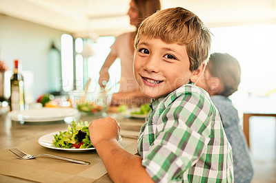 Buy stock photo Cropped portrait of a happy young boy sitting at the table and about to eat lunch with his family