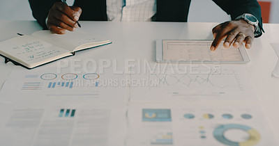 Buy stock photo Shot of an unrecognizable businessman using a digital tablet and writing on a notepad while working inside his office
