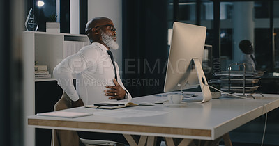 Buy stock photo Shot of a mature businessman suffering from back pain while working late inside his office