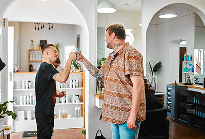 Buy stock photo Cropped shot of a handsome young barber standing with a client in his salon and giving him a fist bump