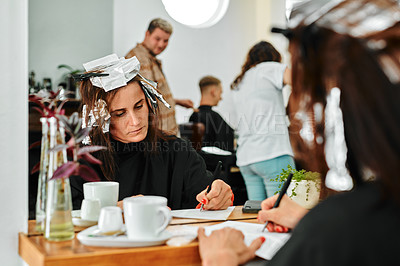 Buy stock photo Cropped shot of an attractive young woman sitting and writing while waiting in a salon with dye in her hair