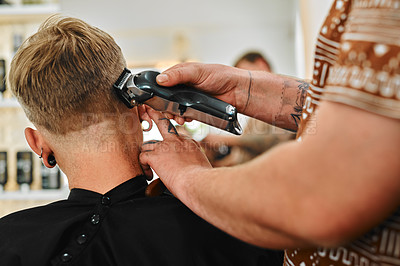 Buy stock photo Cropped shot of an unrecognizable barber standing and shaving a client's hair in his salon
