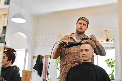 Buy stock photo Cropped shot of a handsome young barber standing in his salon and blow drying his client's hair
