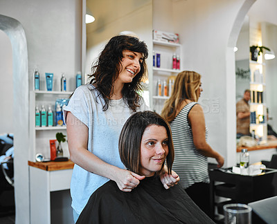 Buy stock photo Cropped shot of an attractive young hairdresser standing and checking the length of a client's hair in the salon