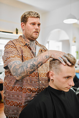 Buy stock photo Cropped shot of a handsome young barber standing and styling a client's hair after a cut in the salon