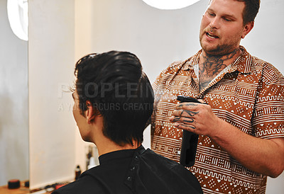 Buy stock photo Cropped shot of a handsome young barber using a spray bottle to wet his client's hair before a cut