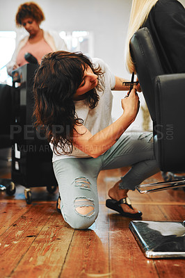 Buy stock photo Full length shot of an attractive young hairdresser kneeling and cutting a client's hair in her salon