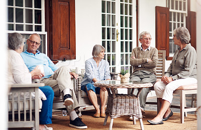 Buy stock photo Full length shot of a group of senior citizens sitting together and enjoying a day out on the veranda