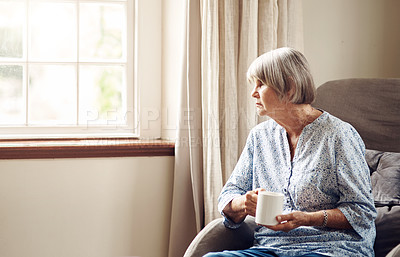 Buy stock photo Shot of a senior woman having coffee and looking thoughtfully out of a window