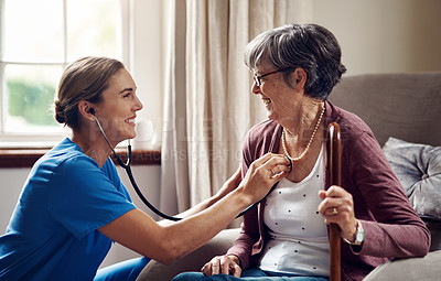 Buy stock photo Shot of a nurse examining a senior woman with a stethoscope at home