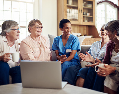 Buy stock photo Cropped shot of an attractive young nurse sitting and watching a movie on a laptop with her senior patients