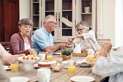 Buy stock photo Cropped shot of a senior man offering his female friend a biscuit during a tea party outdoors