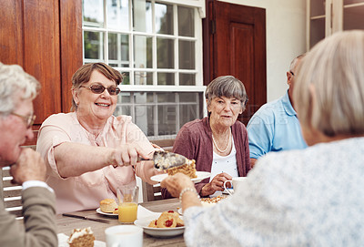 Buy stock photo Cropped shot of a happy senior woman serving carrot cake to her friend during a tea party outdoors