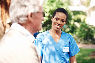 Buy stock photo Cropped shot of an attractive young nurse standing with her senior patient during a day outdoors
