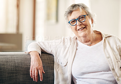 Buy stock photo Shot of a happy senior woman relaxing on the sofa at home