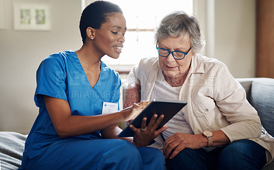 Buy stock photo Shot of a senior woman using a digital tablet with a nurse on the sofa at home
