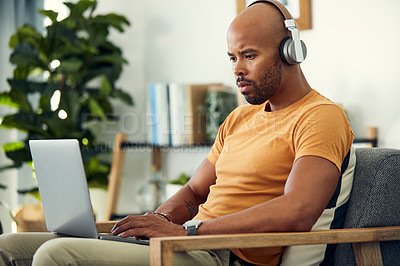 Buy stock photo Shot of a man wearing his headphones while using a laptop at home