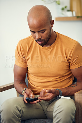 Buy stock photo Shot of a young man checking his blood sugar levels while sitting on the sofa at home