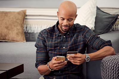 Buy stock photo Cropped shot of a young man using his credit card while using his cellphone