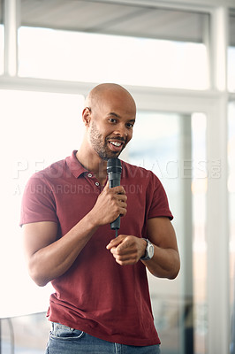 Buy stock photo Cropped shot of a handsome young man speaking over a microphone