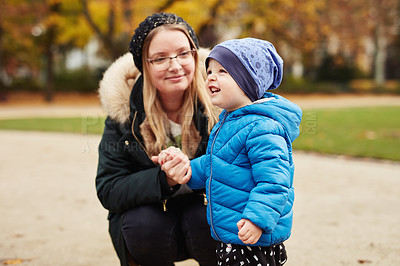 Buy stock photo Cropped shot of an adorable little boy looking amused while spending time with his mother in a park in autumn