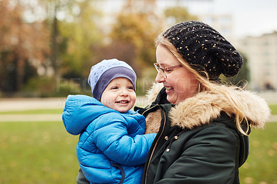 Buy stock photo Cropped shot of an affectionate young mother carrying her little  son while standing in a park in autumn