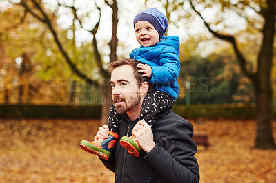 Buy stock photo Cropped shot of an affectionate young father carrying his little son on his shoulders in a park in autumn