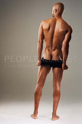 Buy stock photo Rearview shot of a handsome young man posing in underwear against a grey background