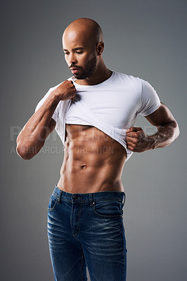 Buy stock photo Shot of a handsome young man taking off his t-shirt against a grey background