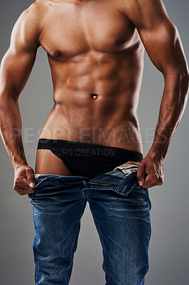 Buy stock photo Rearview shot of an unrecognizable muscular young man undressing against a grey background