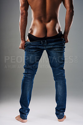 Buy stock photo Rearview shot of an unrecognizable young man undressing against a grey background