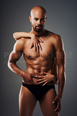 Buy stock photo Portrait of a handsome young man posing in underwear against a grey background