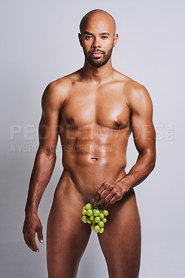 Buy stock photo Shot of a naked man posing with a bunch of grapes covering his genital area against a grey background