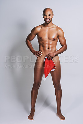 Buy stock photo Full length shot of a naked man posing with a Christmas hat covering his genital area against a grey background