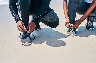 Buy stock photo Cropped shot of two unrecognizable people tying their shoe laces before going for a jog outside next to a beach during the day