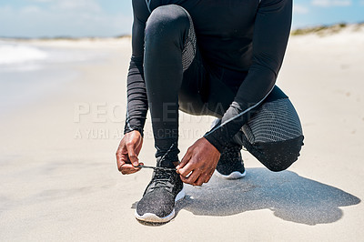 Buy stock photo Cropped shot of an unrecognizable man tying his shoe laces before starting with training exercises outside next to a beach during the day