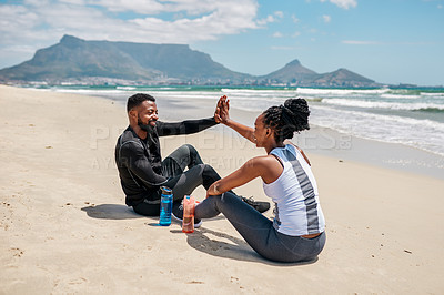 Buy stock photo Shot of a cheerful young couple giving each other a high five while being seated on the ground next to a beach outside during the day