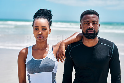 Buy stock photo Portrait of a confident young couple standing together on a beach outside during the day