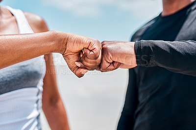 Buy stock photo Closeup of an unrecognizable couple locking fists while standing on a beach together outside during the day