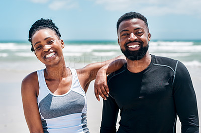 Buy stock photo Portrait of a cheerful young couple standing together on a beach outside during the day