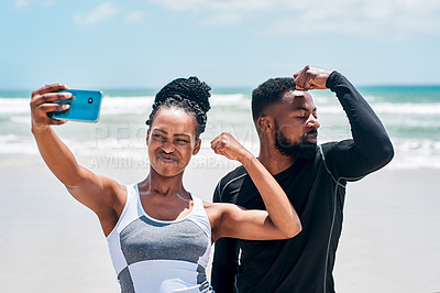 Buy stock photo Cropped shot of a cheerful young couple flexing their biceps while taking a self portrait with a cellphone outside on a beach during the day