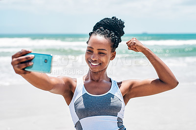 Buy stock photo Cropped shot of a cheerful young woman flexing her bicep while taking a self portrait with a cellphone outside on a beach during the day