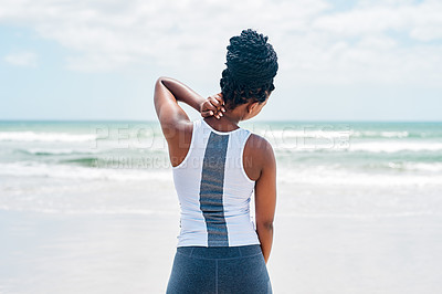 Buy stock photo Rearview shot of a stressed out young woman holding her neck due to pain while standing on a beach outside during the day
