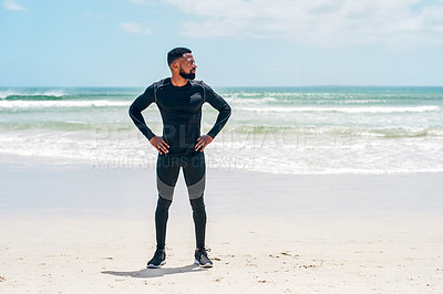 Buy stock photo Cropped shot of a confident young man standing with his hands on his hips while looking into the distance outside on a beach during the day