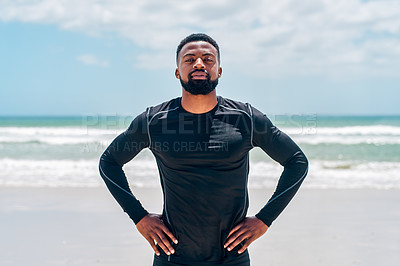 Buy stock photo Portrait of a confident young man standing with his hands on his hips  outside on a beach during the day