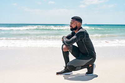 Buy stock photo Shot of a confident young man seated on the beach while contemplating outside on a beach during the day