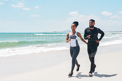 Buy stock photo Shot of a cheerful young couple having a jog together outside on a beach during the day