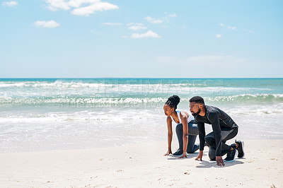Buy stock photo Shot of a confident young couple kneeling on the ground ready to race each other outside on the beach during the day